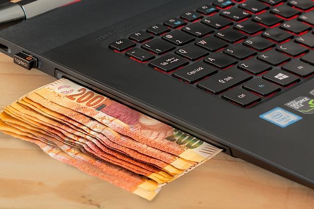 komputer z wystającymi pieniędzmi
