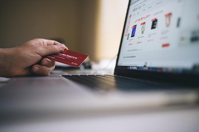 mężczyzna z kartą płatniczą przy komputerze